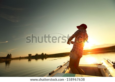 Young man fishing from a boat at sunset - stock photo
