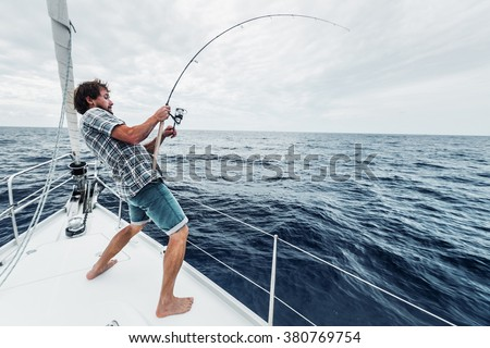 Young man fishing hard in open sea from sail boat