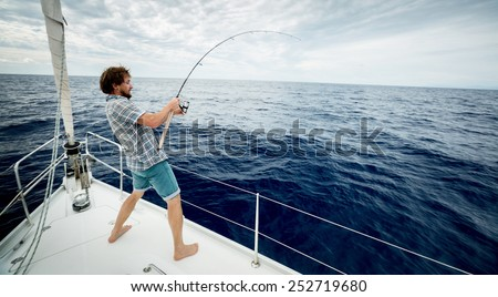 Young man fishing in open sea from sail boat - stock photo