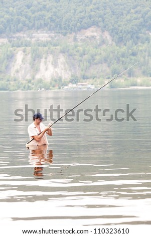 young man fishing in the river - stock photo