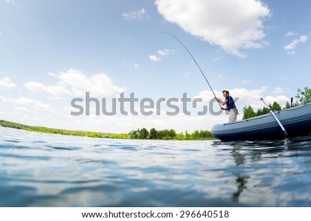 Young man fishing on the fresh water pond at sunny day - stock photo