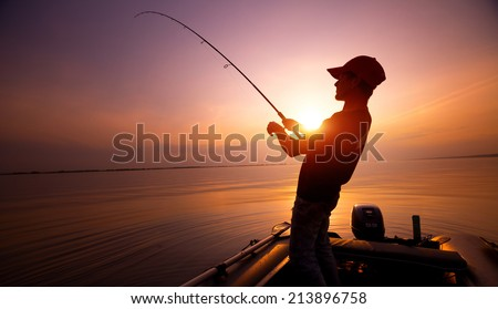 Young man fishing on wide river from the boat at sunset - stock photo