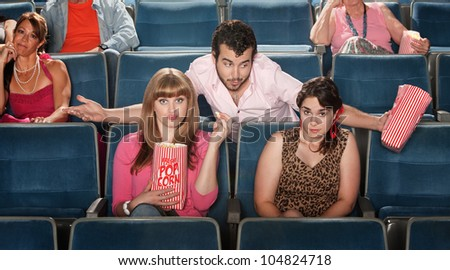 Young man flirts with girls in a theater - stock photo