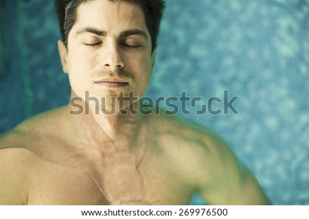 Young man floating in the swimming pool - stock photo