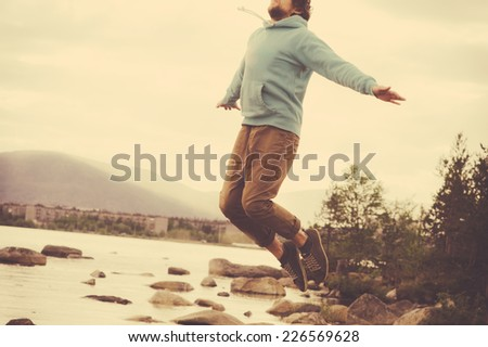 Young Man Flying levitation jumping outdoor relax Lifestyle Travel happiness spiritual concept retro film colors - stock photo