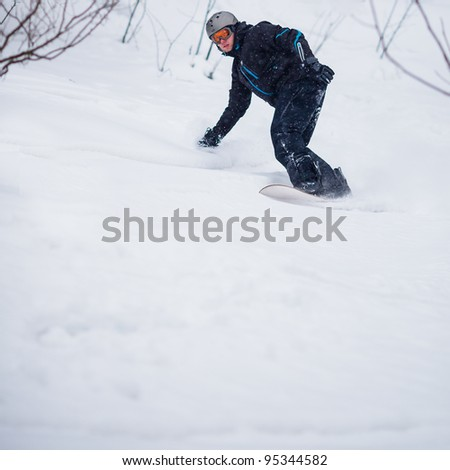 Young man freeride snowboarding off-piste in snow in a mountain resort  on a snowy winter day - stock photo