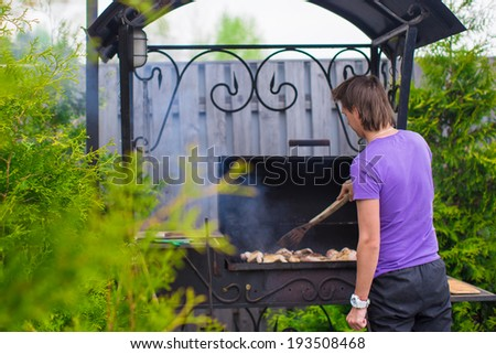 Young man fries steaks on the grill outdoor in his yard - stock photo