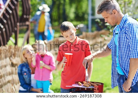 Young man frying sausages on grill outdoors with his son near by