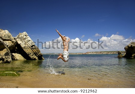Young man full of energy jumping on the beach