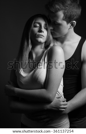 Young man gently embraces girl. Low key. Black and white