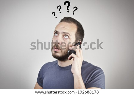 young man gesturing while answering smart phone not understood - stock photo