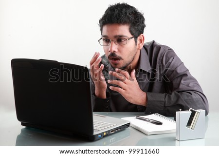 Young man gets shocked in front of his laptop