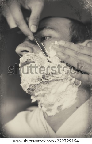 Young man getting an old-fashioned shave at the barber shop. Closeup, retro styled black and white imagery - stock photo