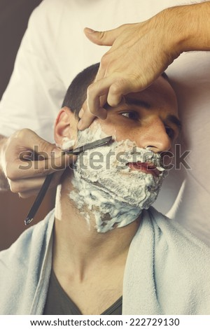 Young man getting an old-fashioned shave at the barber shop. Closeup, retro styled imagery - stock photo