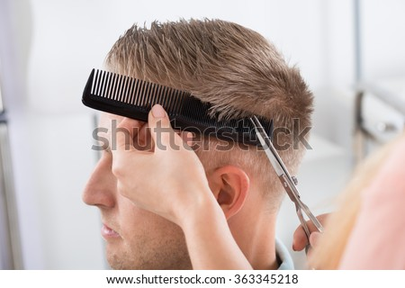 Young man getting haircut from female hairdresser at salon