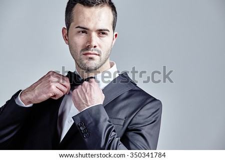 Young man getting ready isolated on grey - stock photo