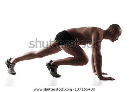 Young man getting ready to run, he is down in his runners stance, on white background - stock photo