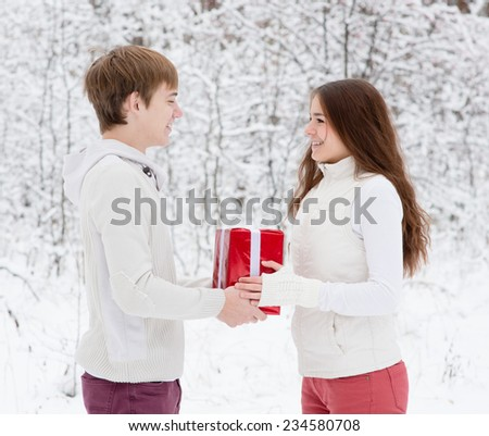 young man gives a present to his girlfriend for Christmas - stock photo