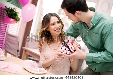 Young man gives present to his beautiful girlfriend