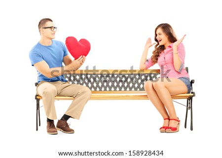 Young man giving a red heart to a surprised female, seated on a bench, isolated on white background - stock photo