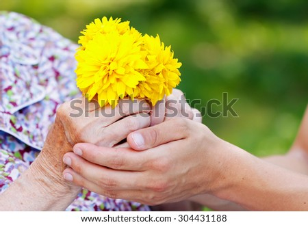 Young man giving a yellow flower to senior woman - stock photo