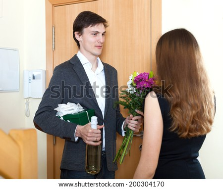 Young man giving gifts to cute woman at home door - stock photo