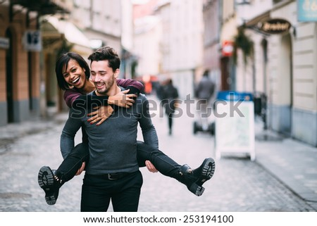 Young man giving girlfirend piggyback ride - stock photo