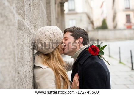 young man giving his girlfriend a rose and kissing celebrating valentines day  - stock photo