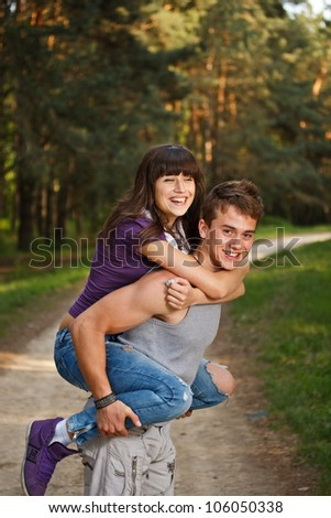 Young man giving piggyback ride to woman - stock photo
