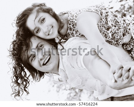 Young man giving piggyback to happy woman outdoors.