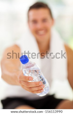 young man giving water bottle in gym - stock photo