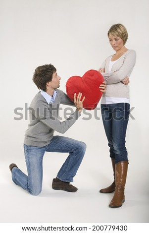 Young man giving woman heart-shaped cushion kneeling - stock photo