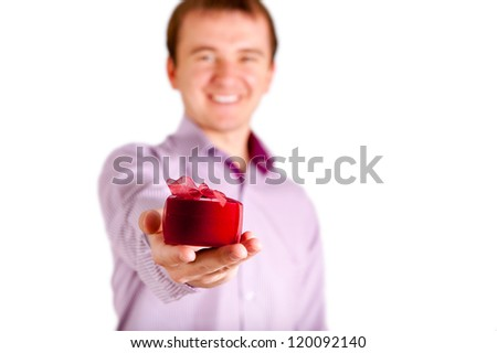 Young man giving you gift and looking at camera, isolated on white background - stock photo