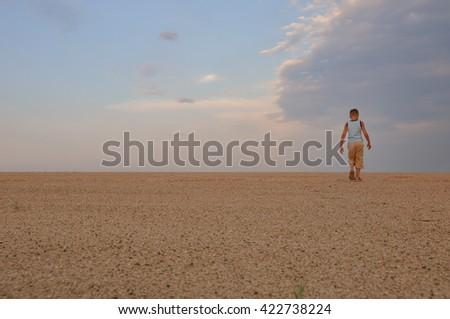 young man go up in sand desert in sundown - stock photo
