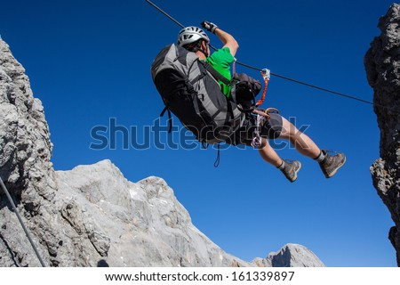 Young man going accross tyrolean traverse on via ferrata (Klettersteig)