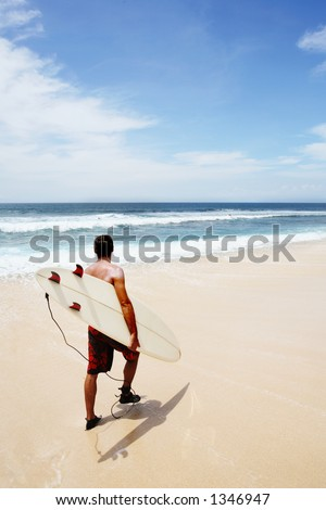 Young man going to surf at Dreamland, Bali