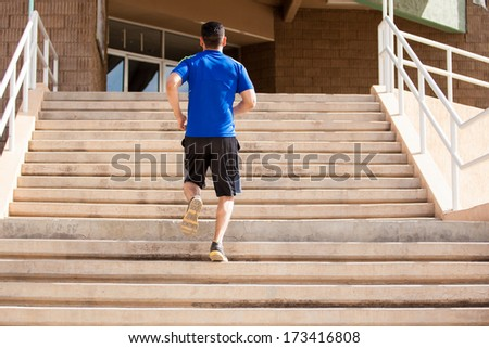 Young man going up a flight of stairs as part of his workout - stock photo