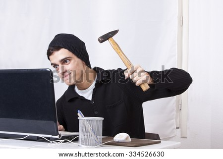 young man hammering computer