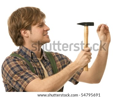 Young man hammering nail, profile view. Isolated on white. - stock photo