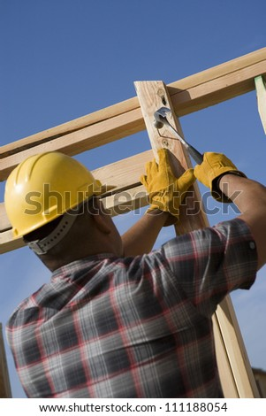 Young man hammering nail to wooden beam at construction site - stock photo