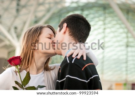 Young man handing over a flower (red rose) to woman and kissing her - stock photo