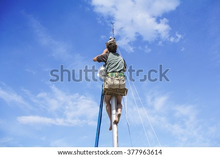 Young man hanging and repairs yacht mast - stock photo
