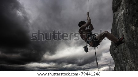Young man hanging on a rope by a cliff