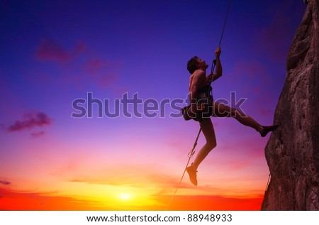 Young man hanging on a rope by a rocky wall over sunset sky background