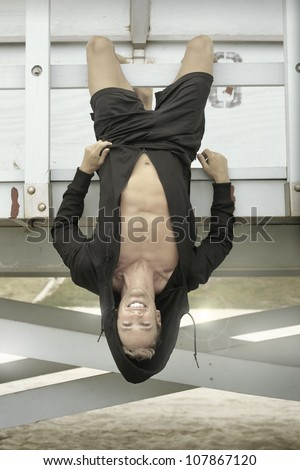 Young man hanging upside down outdoors with nice smile - stock photo