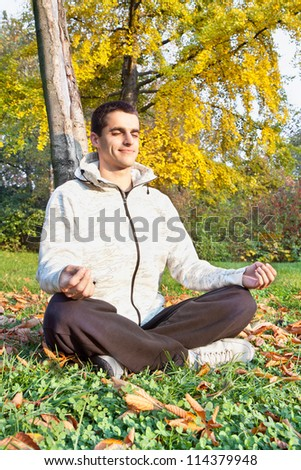 Young man has meditating in autumn park