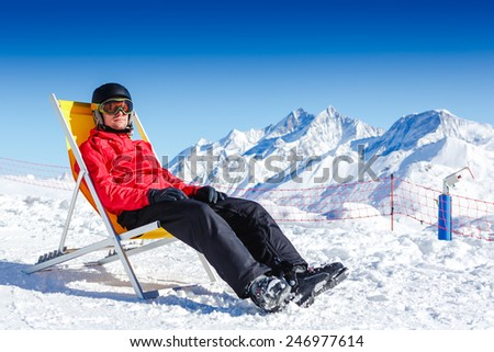 Young man have a rest at mountains in winter. Winter ski vacation