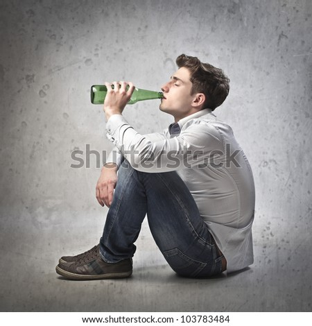 Young man having a beer - stock photo