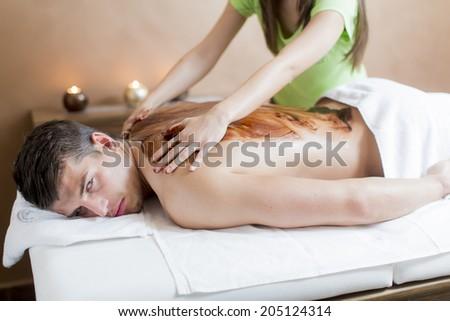 Young man having a chocolate massage - stock photo