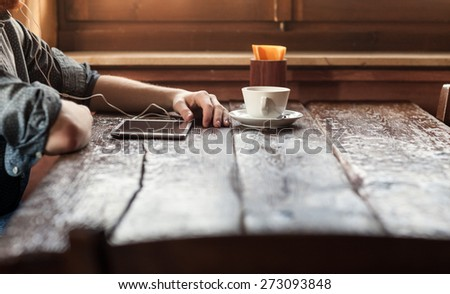 Young man having a coffee break at the bar and listening to music with his tablet using earphones - stock photo